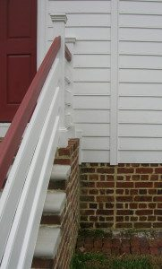 The corner board in the siding and the seam in the brick foundation are visible. This break shows where the original house ended to the right of the front porch. Note the closer bricks on both sides of the seam in the bricks.