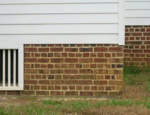 The brick foundation and siding on the kitchen outbuilding do not align with the brick foundation and siding on the main house addition. Note the security bars on the window in the English basement.