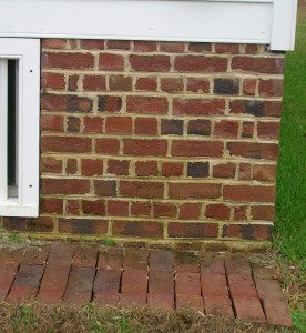 Hand-moulded bricks laid in the English bond pattern with closer bricks used to keep the corner and window edge plumb. Brick ground gutter below.