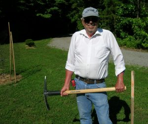 Using a pick-axe to break through the hardpan.